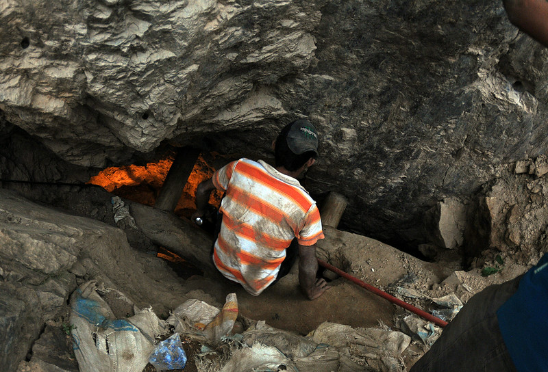 . A man looks into a gold mine where miners are trapped after a landslide in San Juan Arriba, Choluteca, in southern Honduras, early Thursday, July 3, 2014. The entrance to the artisanal mine has a vertical entrance, is located on a steep slope, and operated by local residents. (AP Photo/Fernando Antonio)