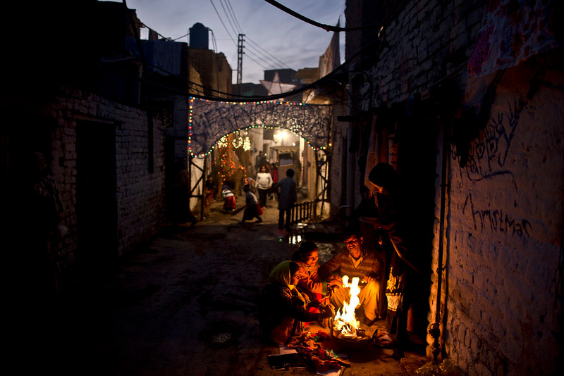 . Pakistani Christian family members gather around a fire to warm themselves from the evening cold in an alley of a Christian neighborhood decorated with festive lights for Christmas in Islamabad, Pakistan, Wednesday, Dec. 24, 2014. (AP Photo/Muhammed Muheisen)