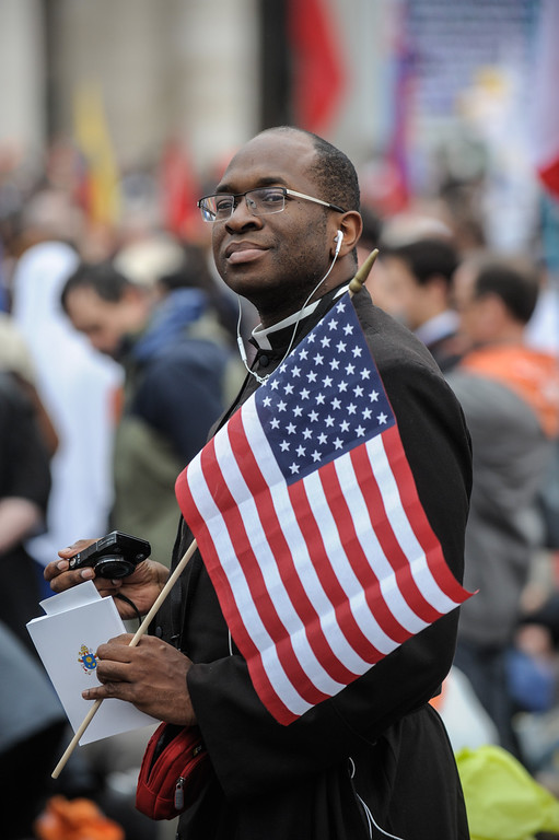 . A priest holds an American flag as he attends the canonisations of Popes John Paul II and John XXIII on April 27, 2014 in Vatican City, Vatican. Dignitaries, heads of state and Royals from Europe and from around the world are to attend the canonisations in the Vatican.  (Photo by Giorgio Cosulich/Getty Images)