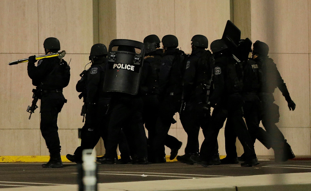 . Officials wearing tactical gear walk outside of Garden State Plaza Mall following reports of a shooter, Monday, Nov. 4, 2013, in Paramus, N.J. Hundreds of law enforcement officers converged on the mall Monday night after witnesses said multiple shots were fired there. (AP Photo/Julio Cortez)