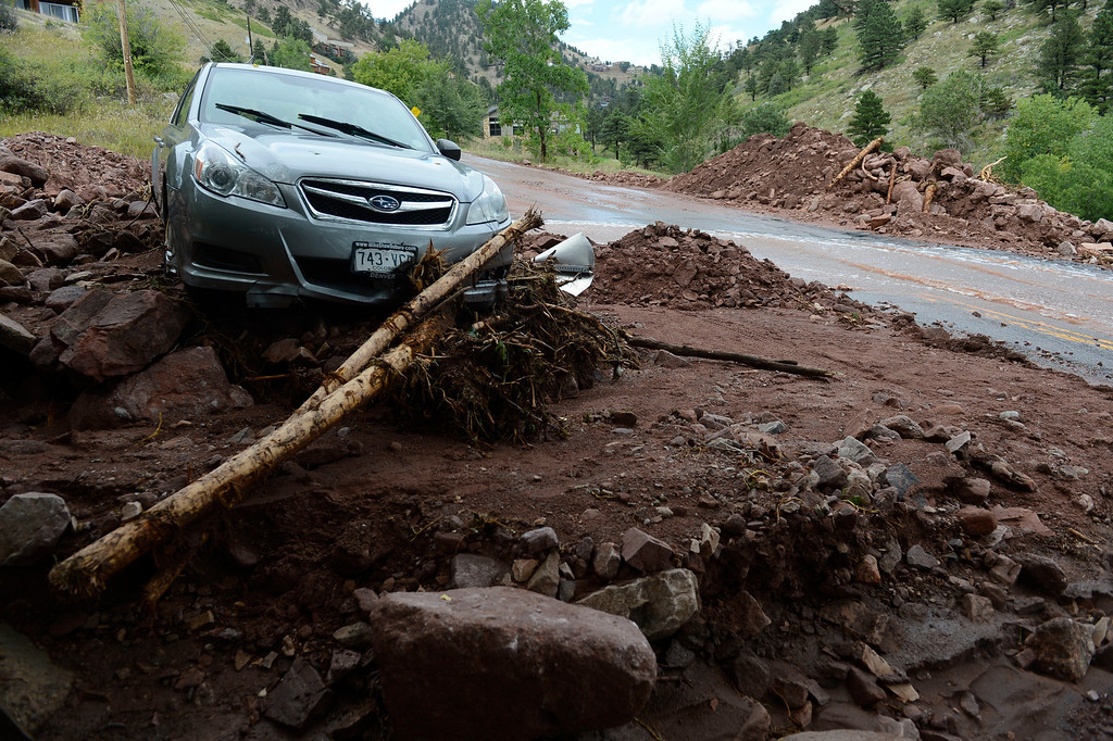 . BOULDER, CO - SEPTEMBER 13: A vehicle stuck in the mud and rocks at the intersection of Linden and S. Cedar Brook Rd. in Boulder Colorado Friday afternoon, September 13, 2013. The car was swept off the road Wednesday evening in a mudslide due to flooding, it had four people inside, all got out, but two people were swept away and killed in the flooding, the other two were accounted for. (Photo By Andy Cross/The Denver Post)