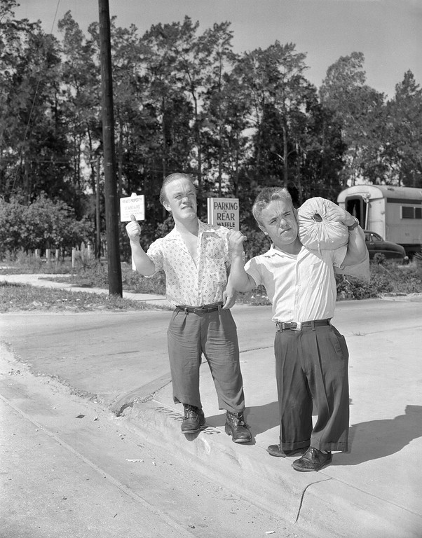 . Roy Smith, left, and Harry Burman, right, two dwarves from London, formerly with Ringling Bros., Barnum and Bailey Circus, get set for a long trip, maybe not to London, but somewhere for a job. They arrived aboard the train returning to circus winter quarters in Sarasota, Fla., July 20, 1956. (AP Photo)
