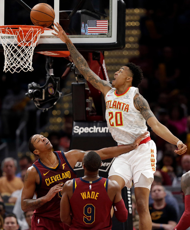 . Atlanta Hawks\' John Collins (20) drives to the basket against Cleveland Cavaliers\' Channing Frye (8) and Dwyane Wade (9) in the second half of an NBA basketball game, Sunday, Nov. 5, 2017, in Cleveland. (AP Photo/Tony Dejak)