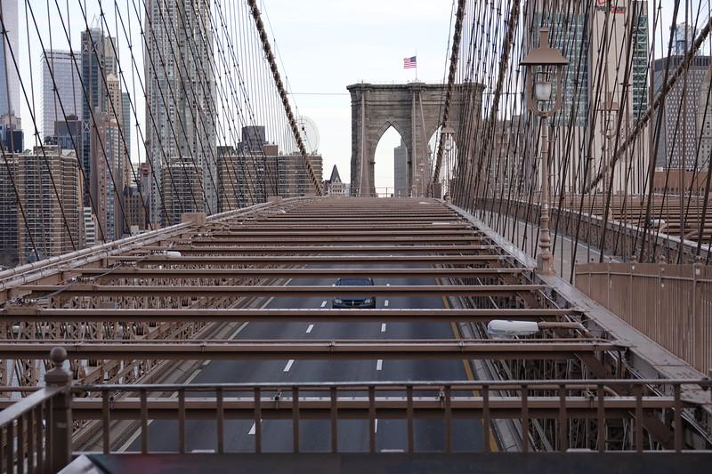 Traffic pounds across the Brooklyn Bridge under the feet of pedestrians.