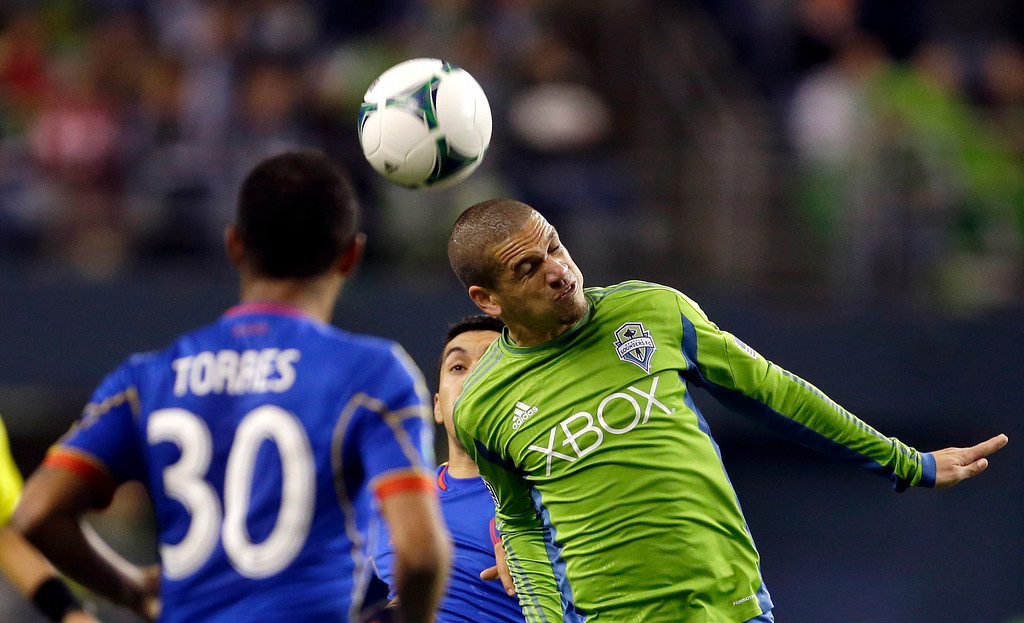 . Seattle Sounders\' Osvaldo Alonso, right, heads the ball as Colorado Rapids\' Gabriel Torres (30) watches in the first half of a knockout-round match in the MLS Cup soccer playoffs Wednesday, Oct. 30, 2013, in Seattle. (AP Photo/Ted S. Warren)