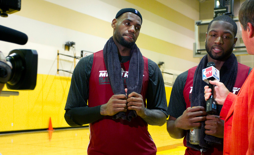 . Miami Heat players LeBron James, left, and Dwyane Wade talk to reporters after an NBA basketball practice in Miami, on Friday, Dec. 9, 2011. (AP Photo/J Pat Carter)