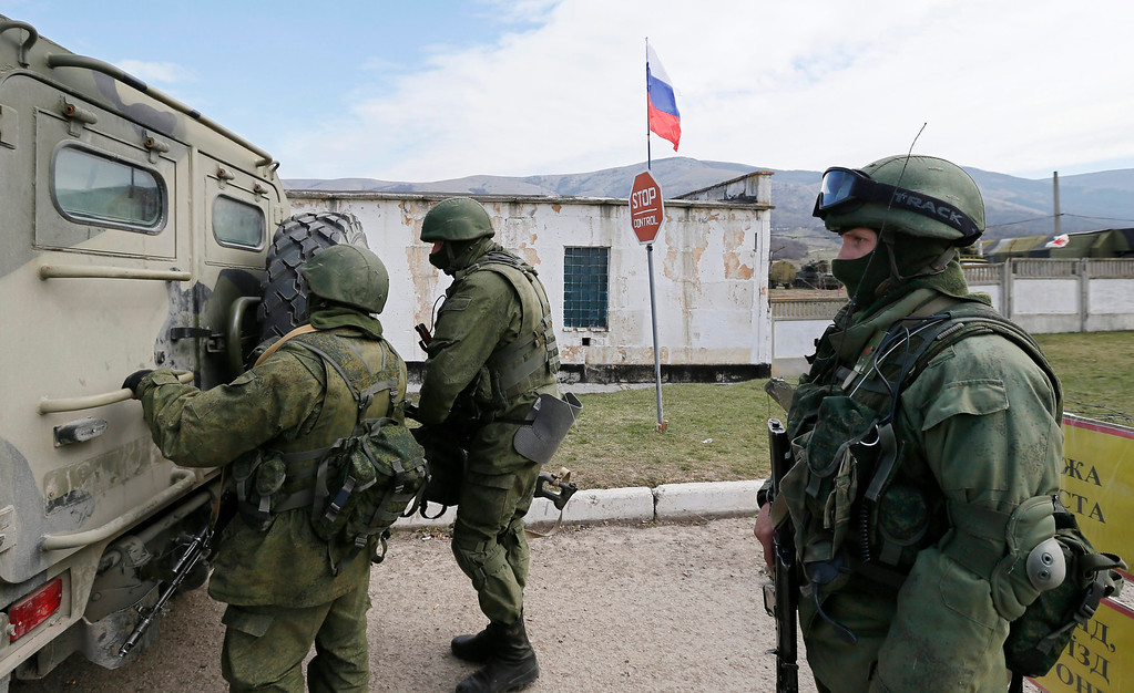 . A Russian flag flutters in the  background as a group of armed men in military uniform open a military vehicle outside the territory of a Ukrainian military unit in the village of Perevalnoye, outside Simferopol, Ukraine, 14 March 2014.Russia moved more soldiers and armor into the Crimea region 14 March amid further threats to invade other parts of the country (Ukraine).  EPA/YURI KOCHETKOV