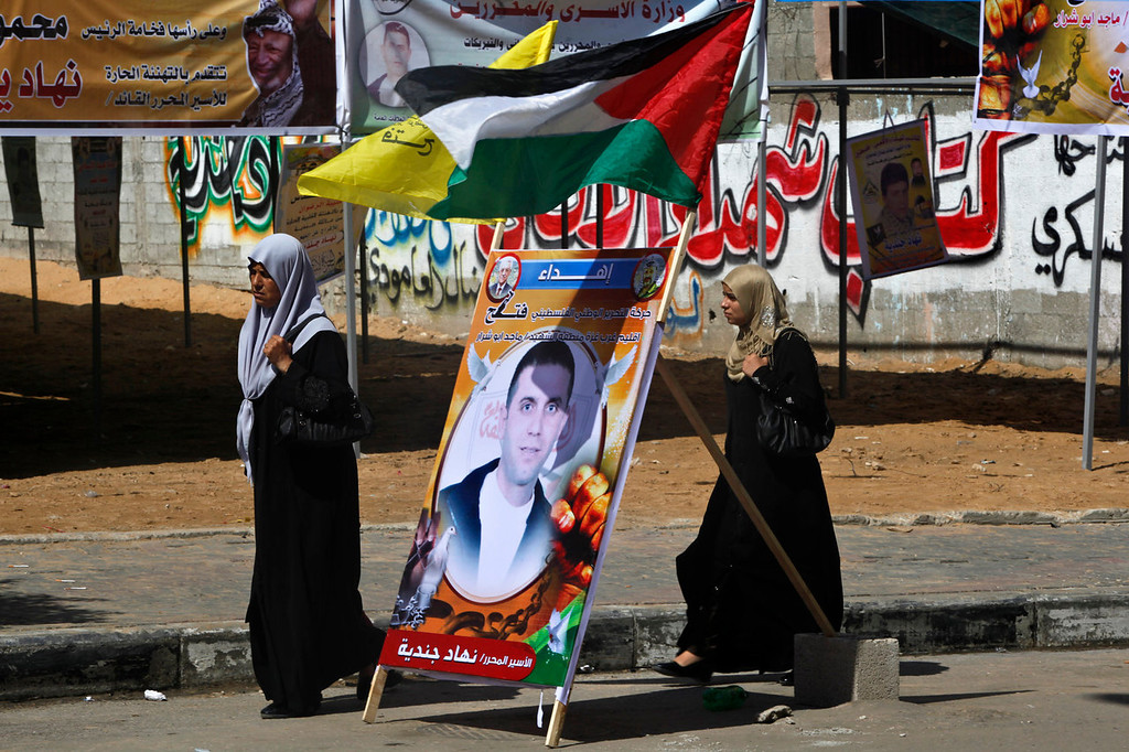 ". Palestinian women walk past a poster of released Palestinian prisoner, Nehad Jondiya, after 24 years spent at Israeli jail, in front of his family house in Gaza City, Wednesday, Aug. 14, 2013. Israelis and Palestinians were to hold their first formal peace talks on home turf in the Middle East in nearly five years Wednesday, hours after Israel released 26 long-held Palestinian prisoners who were given a boisterous homecoming by cheering crowds. Arabic reads, ""Al Aqsa Martyrs\' Brigade, a militia linked to the Fatah movement welcomed the release of Nehad Jondiya.\"" (AP Photo/Adel Hana)"