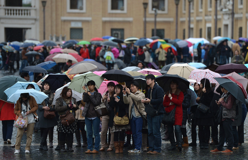 . People walk on St Peter\'s square on the second day of the conclave on March 13, 2013 at the Vatican. The 115 cardinals held a first inconclusive vote in the Sistine Chapel yesterday as they began the process of finding a successor to Benedict XVI, who brought a troubled eight-year papacy to an abrupt end by resigning last month.    AFP PHOTO / GABRIEL BOUYS/AFP/Getty Images