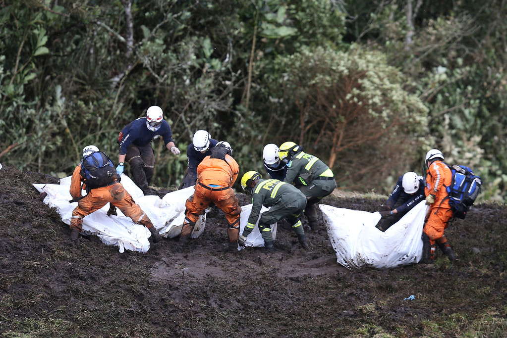 . Rescue workers move the bodies of victims of an airplane crash towards a waiting helicopter, in La Union, near Medellin, Colombia, Tuesday, Nov. 29, 2016. The chartered plane was carrying a Brazilian soccer team to the biggest match of its history when it crashed into a Colombian hillside and broke into pieces, killing 75 people and leaving six survivors, Colombian officials said Tuesday. (AP Photo/Fernando Vergara)