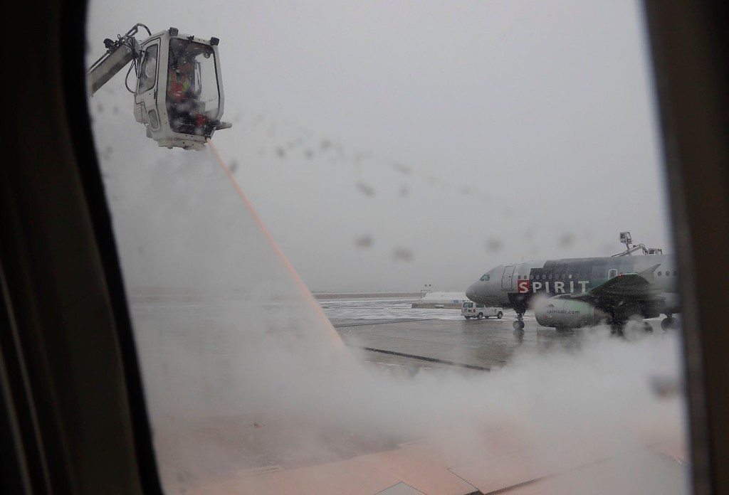 . As snow falls, workers de-ice a Delta aircraft after de-icing the Spirit Air aircraft in the background on the tarmac at Baltimore-Washington International Airport, in Baltimore, Md., Saturday, Jan. 7, 2017. Winter storms along the east coast have caused many flight delays. (AP Photo/Carolyn Kaster)
