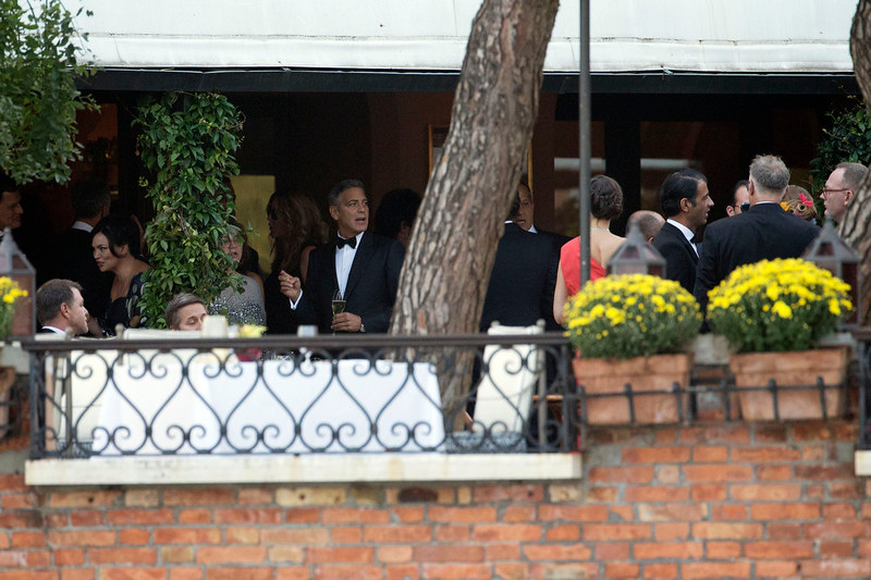 . George Clooney holds a glass during a cocktail with guests at the Cipriani hotel prior to his wedding with Amal Alamuddin, in Venice, Italy, Saturday, Sept. 27, 2014. (AP Photo/Andrew Medichini)