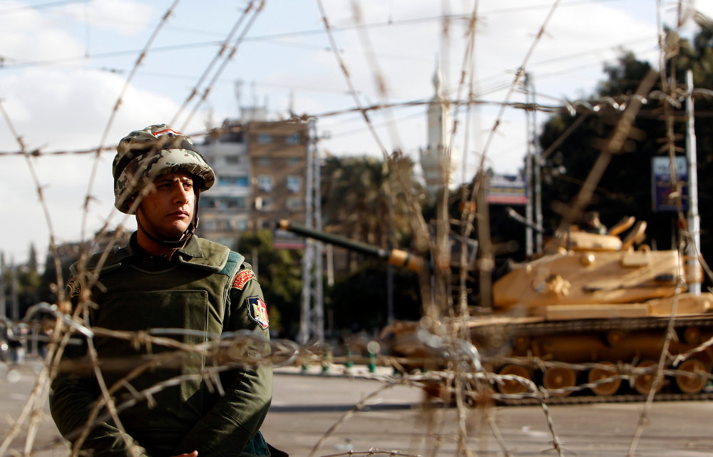 Description of . A member of the Republican Guard stands behind a barbed wire barricade, as the Guard blocks a road leading to the presidential palace in Cairo December 7, 2012. Egyptian opposition leaders rejected a national dialogue on Friday that had been proposed by Islamist President Mohamed Mursi as a way out of a crisis that has polarised the nation and provoked deadly clashes in the streets.        REUTERS/Mohamed Abd El Ghany