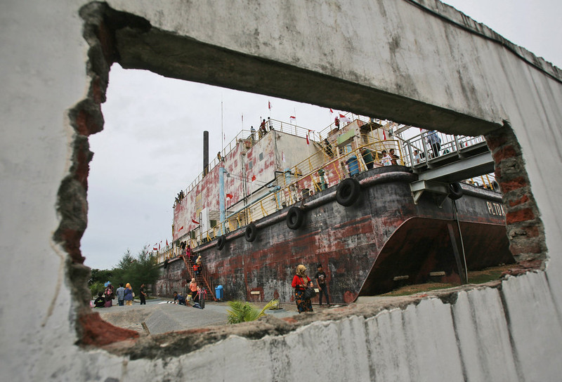 . People are seen through a hole in the wall of a damaged building, as they visit a giant steel barge that housed a diesel power generator swept ashore by the Indian Ocean tsunami ten years ago, in Banda Aceh, Aceh province, Indonesia, Friday, Dec. 26, 2014. The devastating Boxing Day tsunami in 2004 struck a dozen countries around the Indian Ocean rim, killing 230,000 people, most of them in Aceh. The power plant is now a major tourist attraction in the provincial capital. (AP Photo/Binsar Bakkara)