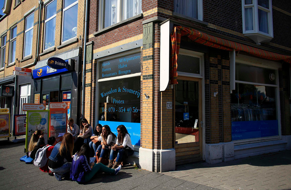 . Spanish nurse Maria Jose Marin (R), 23, sits outside a bank branch next to her twin sister Maria Teresa and other Spanish nurses after opening a bank account in The Hague, June 5, 2013. After months of studying Dutch, a group of young Spanish nurses moved to the Netherlands to take up work, fleeing a dismal job market at home. Spain\'s population dropped last year for the first time on record as young professionals and immigrants who moved here during a construction boom head for greener pastures. Spain\'s jobless rate is 27 percent, and more than half of young workers are unemployed. For Spanish nurses, the Netherlands\' nursing deficit is a boon. Picture taken June 5, 2013. REUTERS/Marcelo del Pozo