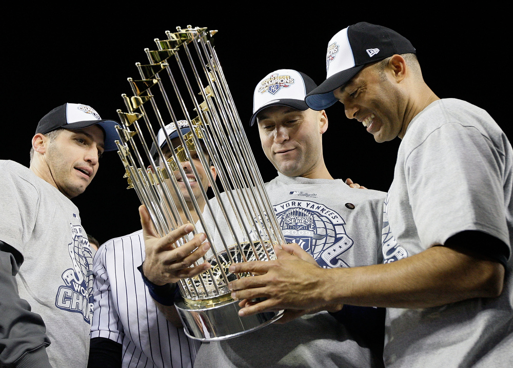 . Andy Pettitte #46, Jorge Posada #20, Derek Jeter #2 and Mariano Rivera #42 of the New York Yankees celebrate with the trophy after their 7-3 win against the Philadelphia Phillies in Game Six of the 2009 MLB World Series at Yankee Stadium on November 4, 2009 in the Bronx borough of New York City.  (Photo by Pool/Getty Images)