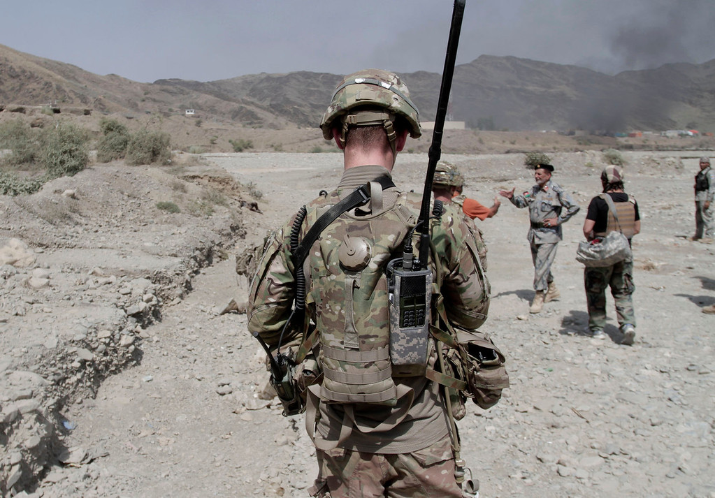 . U.S. soldiers forces investigate the scene of an attack by militants in the Torkham area near the Pakistan-Afghanistan border east of Kabul, Afghanistan, Monday, Sept. 2, 2013. The Taliban claimed responsibility for the strike on a U.S. base in Afghanistan near the border with Pakistan on Monday, setting off bombs, torching vehicles and shutting down a key road used by NATO supply trucks, officials said. Several people were killed.  (AP Photo/Rahmat Gul)