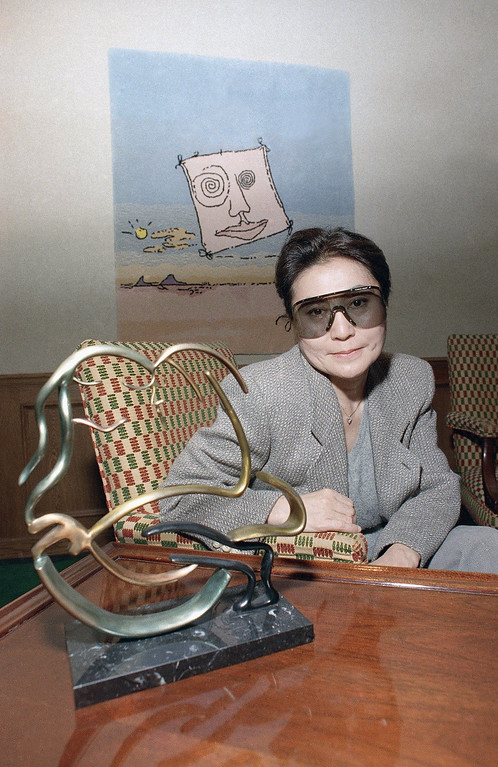 """. Yoko Ono, widow of John Lennon poses with one of his works entitled \""""Bag One\""""  at the opening of a show of previously unreleased Lennon art at a Chicago art gallery on Friday, Feb. 26, 1988 in Chicago.   The collection includes bronze sculpture, stone lithographs, serigraphs, tapestries, and kinetic neon sculpture. (AP Photo/Mark Elias)"""