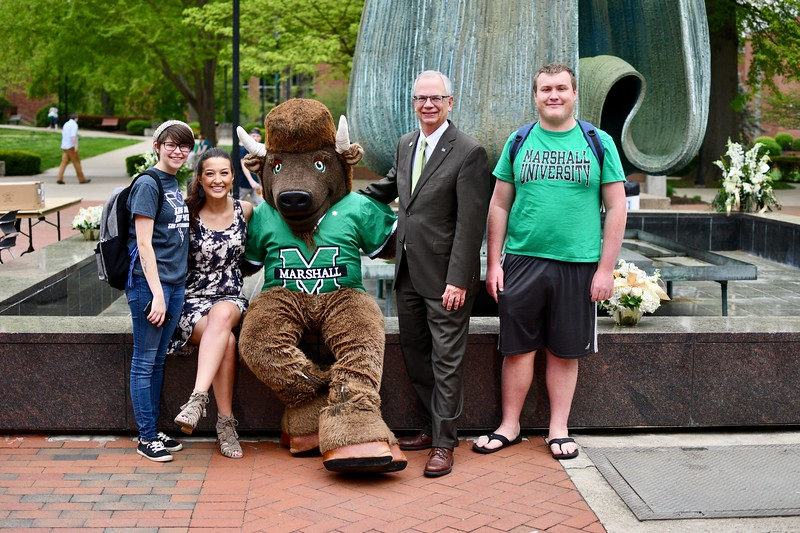President Gilbert with students and Marco