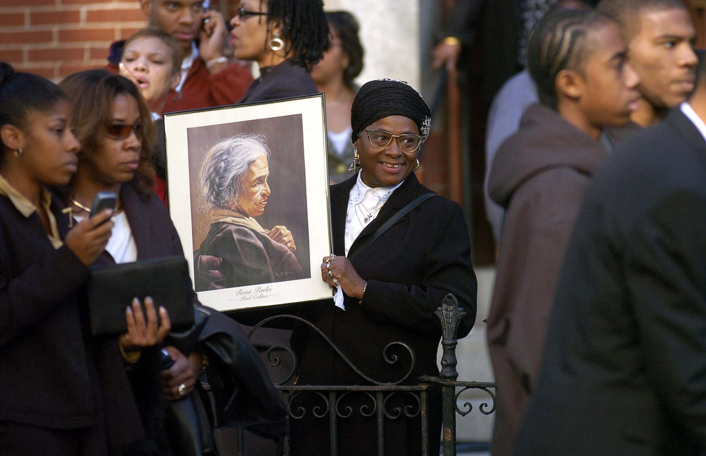 Description of . An unidentified woman holds a portrait of Rosa Parks outside the Metropolitan A.M.E. Church before a memorial service for the late civil rights icon, on Monday, Oct. 31, 2005 in Washington.  Parks, who died last Monday in Detroit, refused to give up her seat on a bus in 1955, sparking the Montgomery bus boycott.   (AP Photo/Kevin Wolf)
