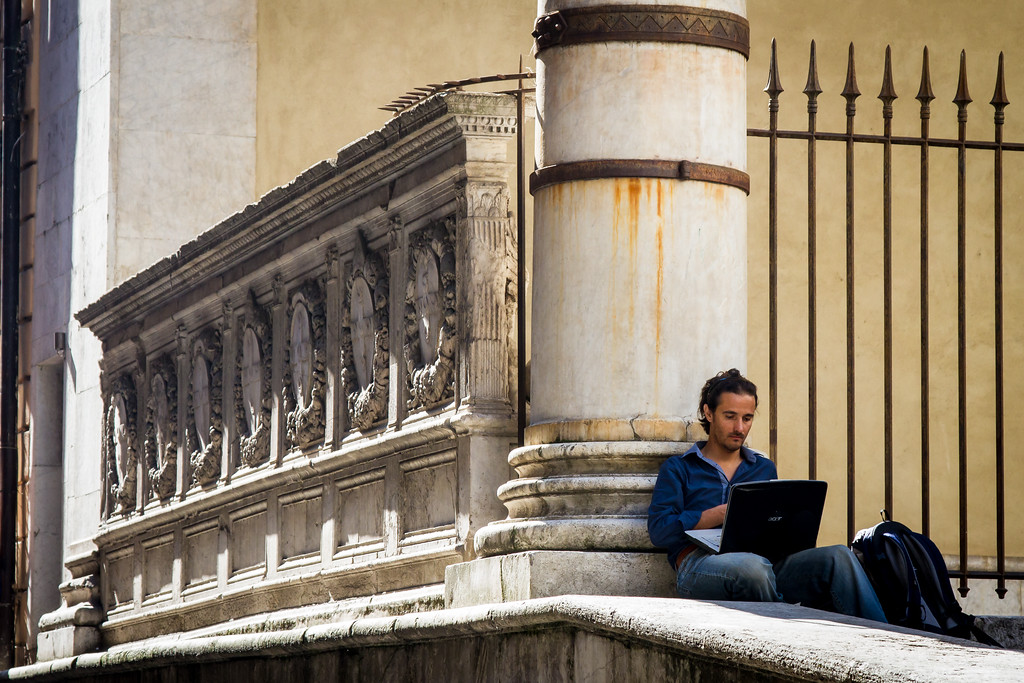 Man with laptop computer with classical architecture