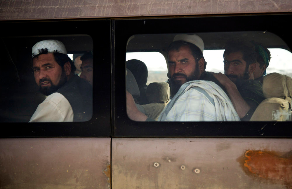 . Afghan men peer out of a bus at a checkpoint manned by Afghan National Civil Order Police on the outskirts of Maidan Shahr, Wardak province, Afghanistan, Sunday, March 10, 2013. Afghan President Hamid Karzai, infuriated by villager reports of forced detentions and mass arrests, gave U.S. Special Forces two weeks to vacate Wardak province, located barely 30 kilometers (24 miles) from the Afghan capital of Kabul. The deadline for their withdrawal expired midnight Sunday, March 10, 2013. (AP Photo/Anja Niedringhaus)