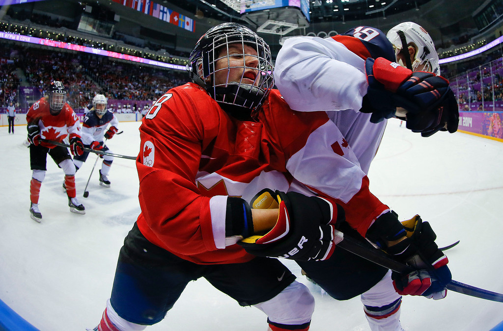 . Laura Fortino of Canada (8) gets an elbow in her mask from Jocelyne Lamoureux of the United States (17) during the third period of the women\'s gold medal ice hockey game at the 2014 Winter Olympics, Thursday, Feb. 20, 2014, in Sochi, Russia. (AP Photo/Matt Slocum)
