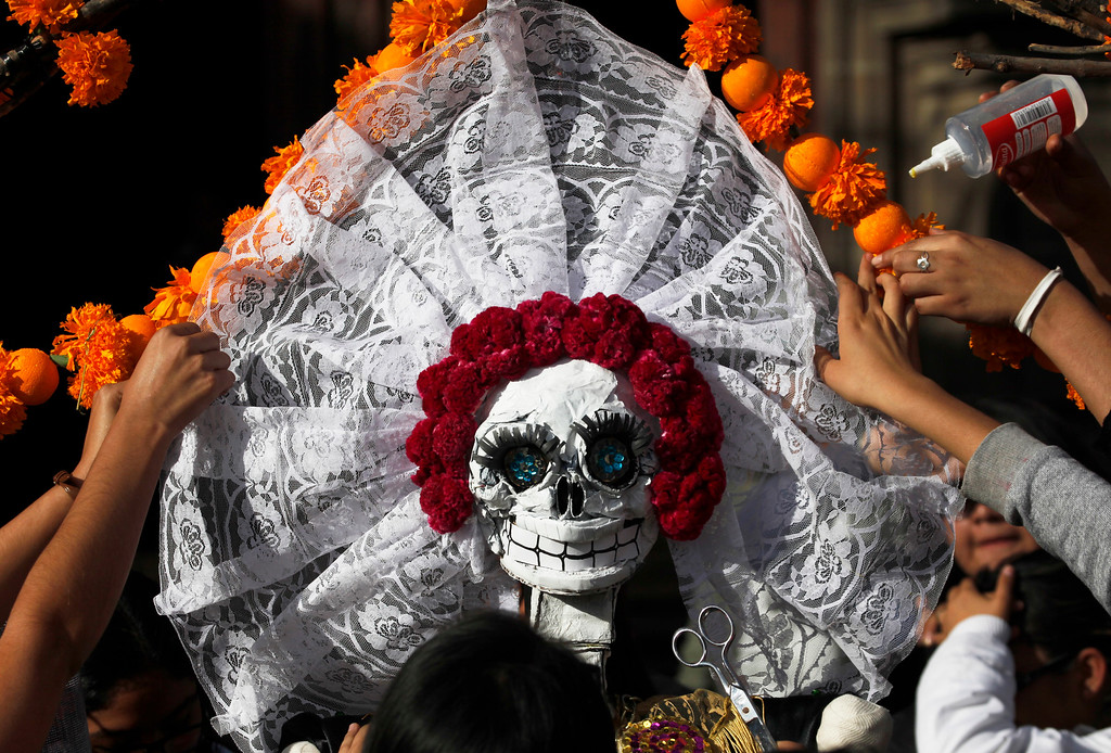 . Residents work on a skeleton representation as part of the Day of the Dead festivities in Mexico City, Thursday, Oct. 27, 2016. The holiday honors the dead as friends and families gather in cemeteries to decorate their loved ones\' graves and hold vigil through the night on Nov. 1 and 2. (AP Photo/Marco Ugarte)