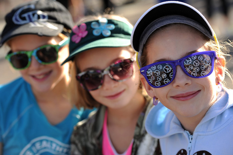 . Sisters Dahlia Linkow, 7, right, her twin Sadie, middle and Shira, left, wore fun glasses as they got ready for the start of the 5K race.  The 31st annual Cherry Creek Sneak had all sorts of distances for this year\'s race.  The Sneak, as it is affectionately named, had a 10 mile, 5 mile, 3.1 mile or 5K, a 1.5 mile Denver\'s 7 Sprint, and a kid\'s fun run for thousands of competitors, runners and walkers that turned out in the Cherry Creek neighborhood of Denver, CO on April 28, 2013.  The race is always held the last Sunday in April. This year participants cheered the national anthem and observed a moment of silence for victims of the Boston Marathon bombing at the start of each race. (Photo by Helen H. Richardson/The Denver Post)