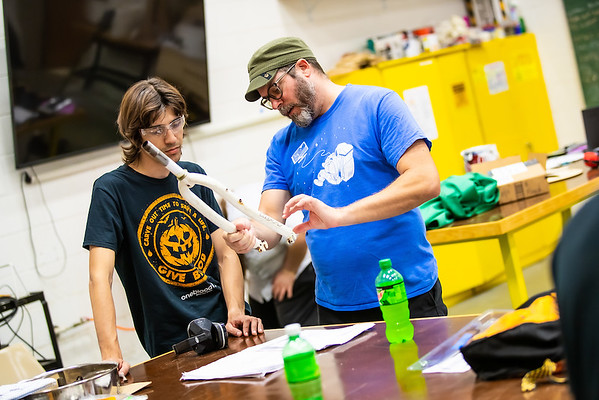 Assistant Professor of Art Ryan Buyssens, right, works with student Kennon Gilson on his human-powered vehicle.