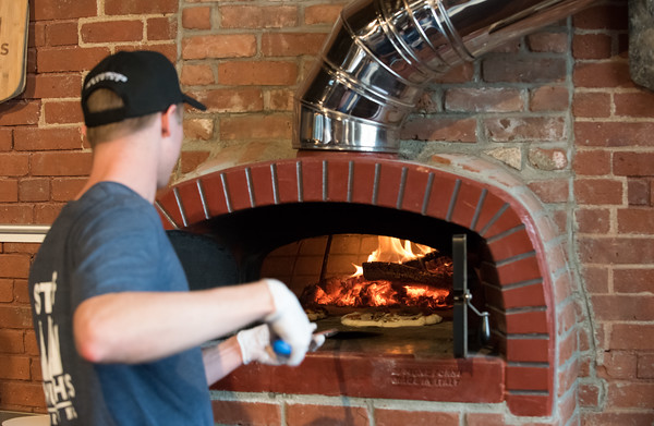 03/30/18 Wesley Bunnell | Staff 5 Churches Brewing held their ribbon cutting with city officials on Friday at noon to a crowd of customers lined down the sidewalk. James Cox cooks individual pizzas in the brewery's brick oven.