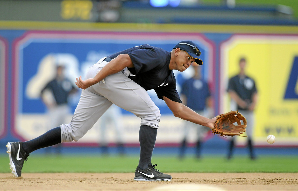 . New York Yankees\' Alex Rodriguez reaches for a ground ball during warm ups for a Class AA baseball game with the Trenton Thunder against the Reading Phillies, Monday, July 15, 2013, in Reading, Pa. Rodriguez is doing a rehab assignment with the Thunder recuperating from hip surgery. (AP Photo/Reading Eagle, Jeremy Drey)