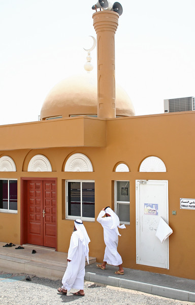 """A small mosque located in the same parking lot as a gas station. Only about 20% of Dubai's residents are locals...these two gentlemen are dressed in local garb. Rich or poor, their wardrobe is the same. Note on the right side of the picture, a sign that indicates entry to the segregated """"Female Prayer Room""""."""