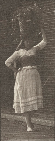 Woman walking and turning around with a 10-lb. basket on head