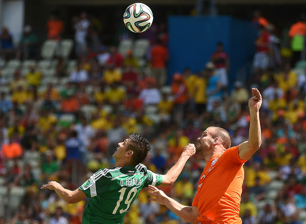 . Mexico\'s forward Oribe Peralta (L) challenges Netherlands\' defender Ron Vlaar for the ball  during a Round of 16 football match between Netherlands and Mexico at Castelao Stadium in Fortaleza during the 2014 FIFA World Cup on June 29, 2014.   EMMANUEL DUNAND/AFP/Getty Images
