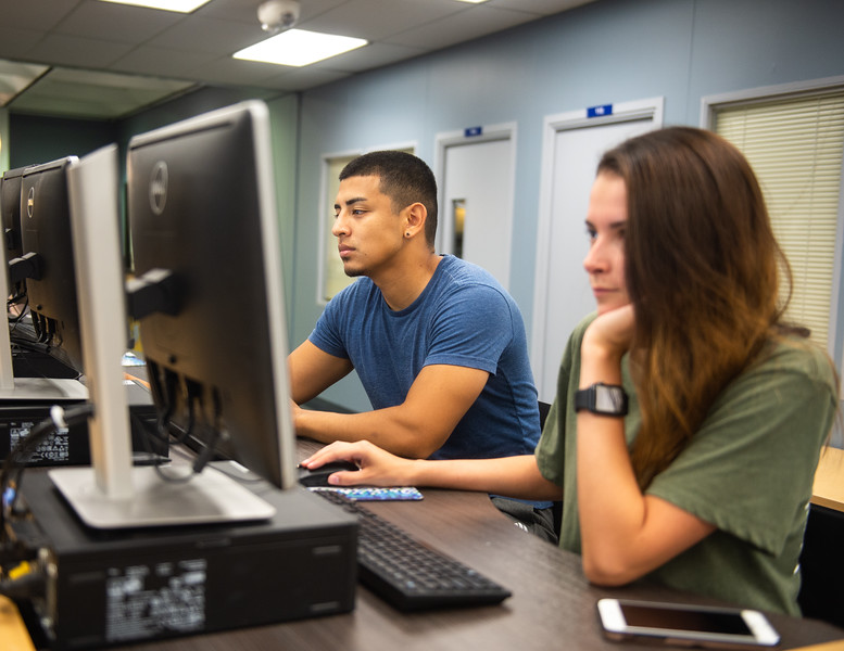 Bradley Robles (left) and Mariah Nicolls work on their summer assignments at the Mary and Jeff Bell Library.