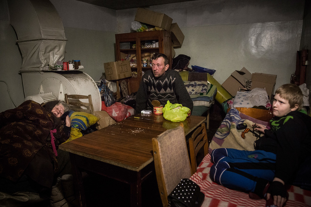 . DEBALTSEVE, UKRAINE - FEBRUARY 25:  Igor Jakoulevna (C) pauses while eating lunch with his family in the basement of an administrative building, where people have been living since August due to continued fighting, on February 25, 2015 in Debaltseve, Ukraine. After approximately one month of fighting, Russian backed rebels successfully forced Ukrainian troops to withdraw from the town of 100,00 people on February 18. Only approximately 11,000 civilians remain in the town. Debaltseve is considered an asset to both Ukrainians and the rebels due to the railway station and it\'s connection to other eastern Ukranian towns.  (Photo by Andrew Burton/Getty Images)