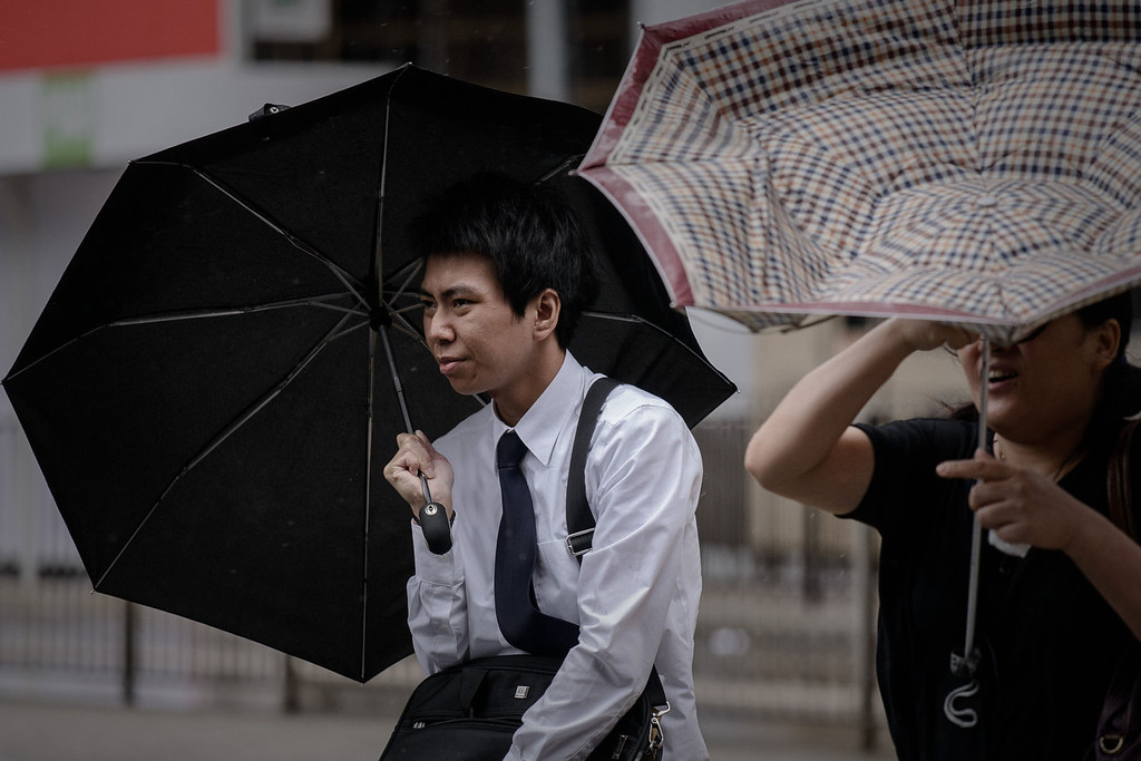 . Pedestrians hold umbrellas in Hong Kong on August 13, 2013 as the city braces for deadly Typhoon Utor which earlier swept through the Philippines. The strongest typhoon to hit the Philippines this year caused floods and landslides, killing at least two people as rescuers raced to reach isolated villages in the storm\'s path.   PHILIPPE LOPEZ/AFP/Getty Images