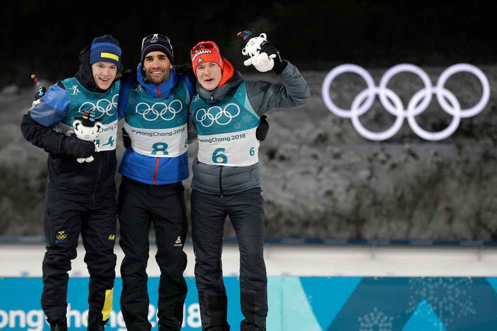 . Silver medalist Sebastian Samuelsson, of Sweden, left, gold medalist Martin Fourcade, of France, center, and bronze medalist Benedikt Doll, of Germany, right, celebrates at the venue ceremony for the men\'s 12.5-kilometer biathlon pursuit at the 2018 Winter Olympics in Pyeongchang, South Korea, Monday, Feb. 12, 2018. (AP Photo/Gregorio Borgia)