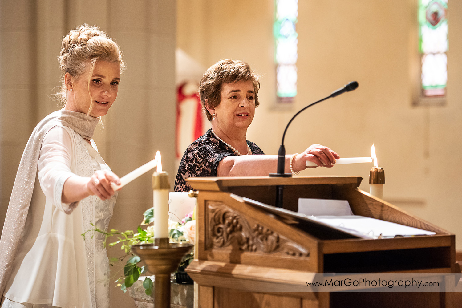 bride and groom's mothers lighting candles during wedding ceremony at Oakland Church of Saint Leo the Great