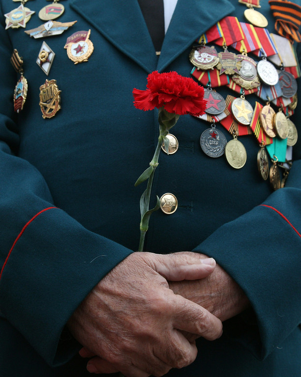 . A decorated veteran holds a red carnation during a Victory Day ceremony at the Unknown Sailor Memorial in the southern Ukrainian city of Odessa on May 9, 2014. Russian President Vladimir Putin took a victory lap in his first visit to Crimea since its annexation by Russia, as fighting in eastern Ukraine left at least 21 dead just days ahead of a separatist vote. AFP PHOTO/ ANATOLII  STEPANOV/AFP/Getty Images