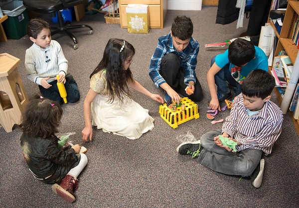 The children of newcomers to Canada play while their parents are interviewed Sunday March 26, 2017 at  Churchill Park United Church. (David Lipnowski for Metro News)