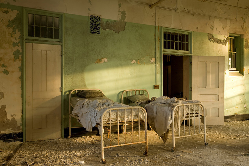 Two beds in a ward dormitory as sunset approaches.  Buffalo State Hospital.