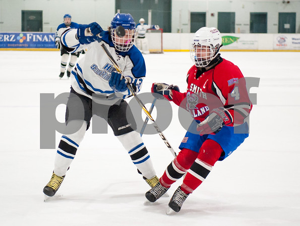 03/01/18 Wesley Bunnell | Staff Hall-Southington defeated EO Smith-Tolland 4-3 in the CCC South semi-final game on Thursday at Veterans Memorial Rink in West Hartford. The puck bounces in front of Nate Zmarlicki (13) and Jason Franklin (4).