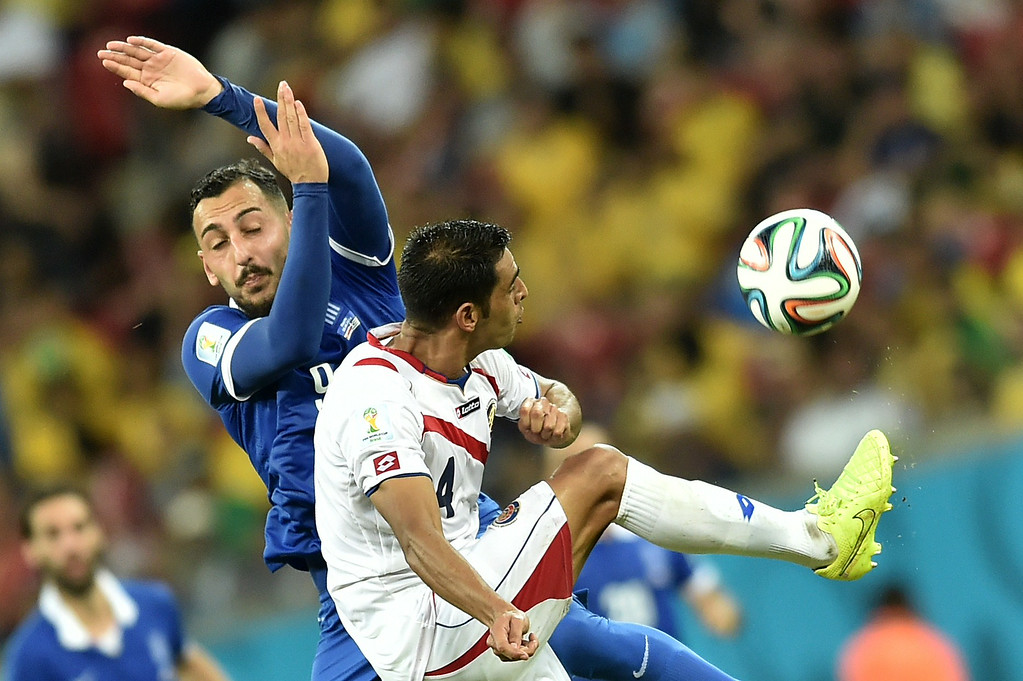 . Greece\'s forward Konstantinos Mitroglou (L) vies with Costa Rica\'s defender Michael Umana, during a Round of 16 football match between Costa Rica and Greece at Pernambuco Arena in Recife during the 2014 FIFA World Cup on June 29, 2014.  AFP PHOTO / ARIS MESSINIS