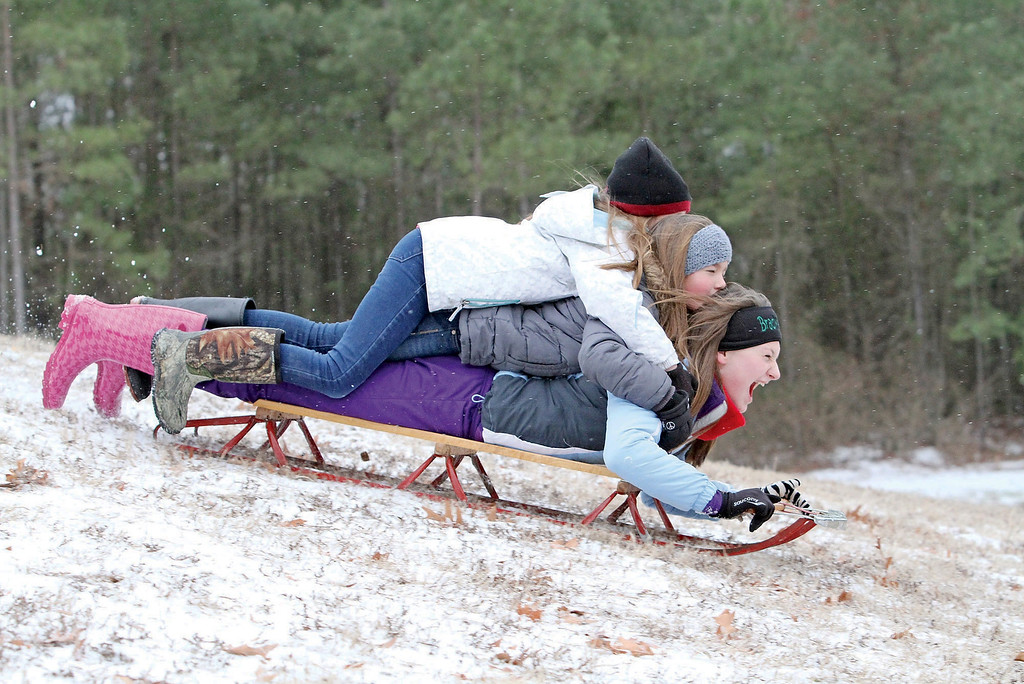 . Madison Jackson, bottom, Madilyn Bonsall, and Julia Jackson sled down a hill on Wednesday, Feb. 12, 2014, in El Dorado, Ark. Most businesses around El Dorado opted to open later in the day after a winter storm dumped a wintery mix on the area. (AP Photo/The El Dorado News-Times, Michael Orrell)