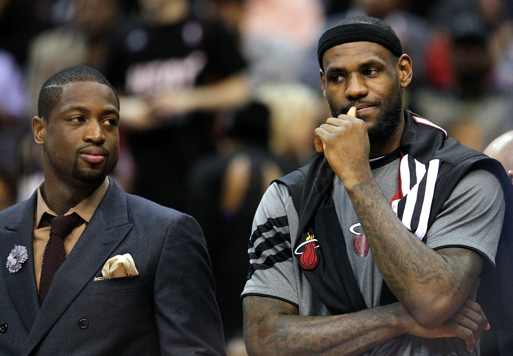 . Miami Heat guard Dwyane Wade, left, and forward LeBron James stand on the sideline during the first half of an NBA basketball game against the Washington Wizards on Thursday, April 26, 2012, in Washington. (AP Photo/Evan Vucci)