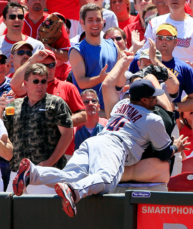 . Cleveland Indians first baseman Carlos Santana falls into a fan trying to catch a foul ball hit by Cincinnati Reds\' Todd Frazier in the fifth inning of a baseball game, Thursday, June 14, 2012 in Cincinnati. (AP Photo/Al Behrman)