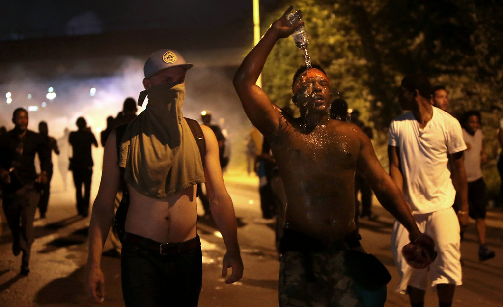 . Protestors retreat from tear gas after marching toward police in Ferguson, Mo., Sunday, Aug. 17, 2014. As night fell Sunday in Ferguson, another peaceful protest quickly deteriorated after marchers pushed toward one end of a street. Police attempted to push them back by firing tear gas and shouting over a bullhorn that the protest was no longer peaceful. (AP Photo/St. Louis Post-Dispatch, Robert Cohen)