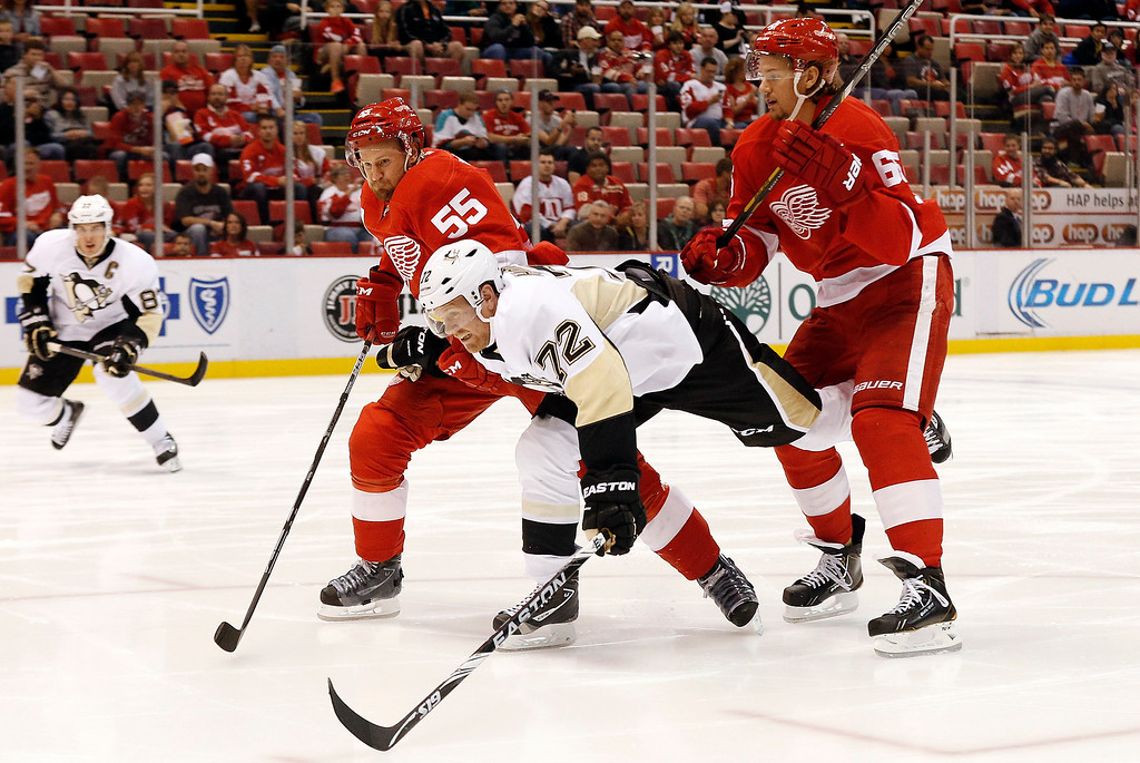 . Pittsburgh Penguins right wing Patric Hornqvist (72), of Sweden, battles Detroit Red Wings defensemen Niklas Kronwall (55), of Sweden, and Danny DeKeyser (65) in the first period of a NHL preseason hockey game in Detroit Wednesday, Oct. 1, 2014. (AP Photo/Paul Sancya)